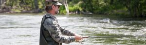 Fisherman catches salmon in mountain river