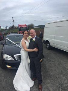 Bridal Car behind bride and groom